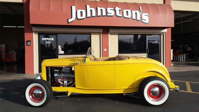 Yellow roadster outside Johnston's Automotive storefront