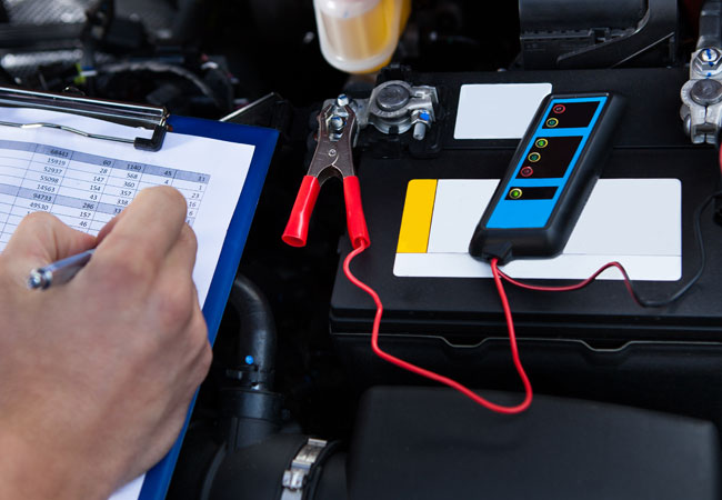 Auto technician checks car battery and electrical performance