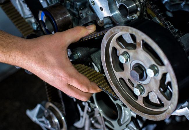 Phoenix mechanic checks slack of timing belt replacement