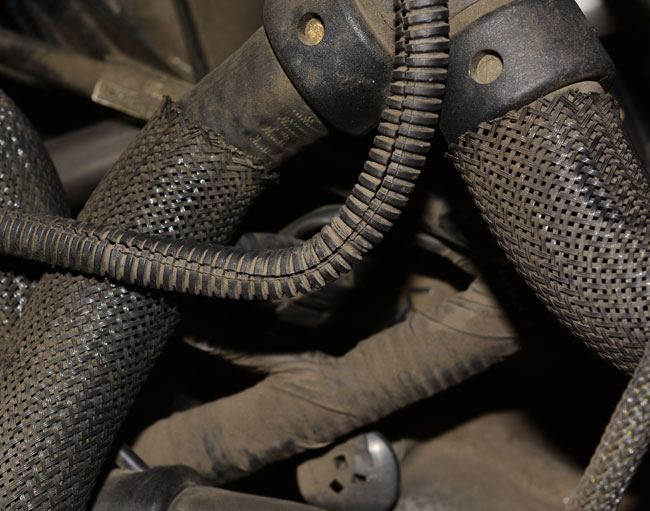 Dirty hoses with protective coverings hiding a leak